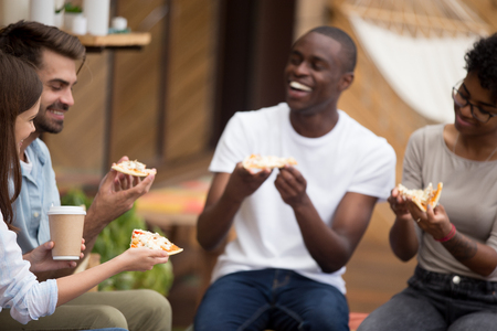 Happy young woman sitting in outdoors restaurant summer cafe spending time with best friends. Students or schoolmates eating pizza drinking coffee enjoying food laughing talking to each other outdoors