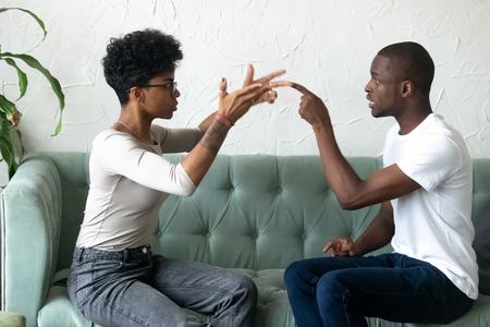 Black married couple sitting on sofa looking at each other sorting out relationships having problems in relations. Emotional boyfriend and girlfriend quarrelling gesturing feels angry and dissatisfied Archivio Fotografico