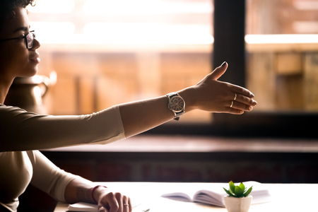 Side view attractive friendly confident african businesswoman sitting at table holds out her hand for a handshake. Business etiquette, partners negotiations, first acquaintance human resources concept Stockfoto