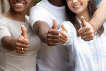 Happy millennial multi-ethnic girls guys standing close to each other showing thumbs up, close up focus on people hands fingers up. Gesture of racial equality, symbol of success and approval concept