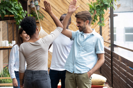 Happy multiracial young people wearing casual clothes standing in summer cafe cozy terrace greeting each other with hand gesture giving high five, showing unity togetherness, celebrating graduation Imagens