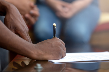 Close up black man holding pen signing contract affirming legal paper with signature. Business negotiations was crowned with success people buying or selling real estate or renting apartments concept