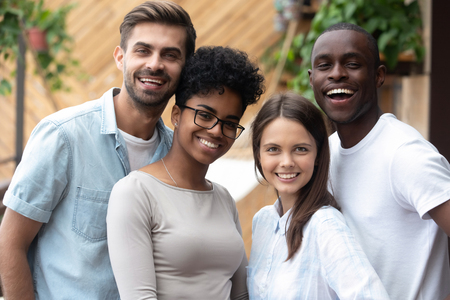 Best friends cheerful diverse people standing together smiling posing for camera. African and caucasian students millennial girls and guys enjoying time together. Concept of multi-ethnic friendship Stock Photo