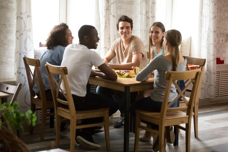 Multiracial laughing friends having fun together, talking, drinking coffee in cafe, young Caucasian woman telling funny story, joke, smiling people enjoying pleasant conversation at meeting Banco de Imagens
