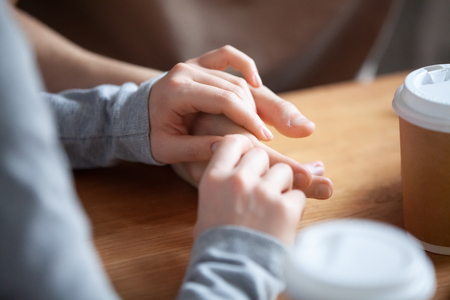 Close up couple in love sitting in cafe together, holding hands, young girlfriend and boyfriend on first date, good relations, trusted friends meeting in public place together, true friendship Stockfoto