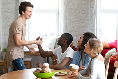 Smiling happy Caucasian man shaking hand of surprised African American friend sitting with girls, greeting at chance meeting in cafe, multiracial people handshaking, friendship concept