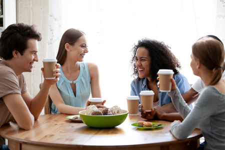 Attractive mixed race girl having fun with friends in cafe, laughing at joke, multiracial students talking about funny news, drinking coffee together, enjoying conversation in coffeehouse