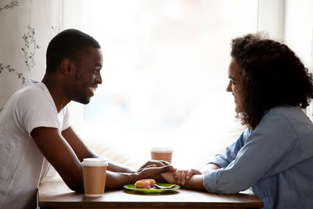 Happy multiracial couple holding hands, enjoying date in cafe, smiling African American boyfriend looking in eyes to attractive girlfriend, having pleasant conversation, spending time together Stock Photo