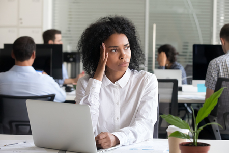 Black mixed race female office worker sitting at desk in coworking space feels unwell unhealthy suffers from headache. Millennial african woman thinking having problem or doubt unsure making decision