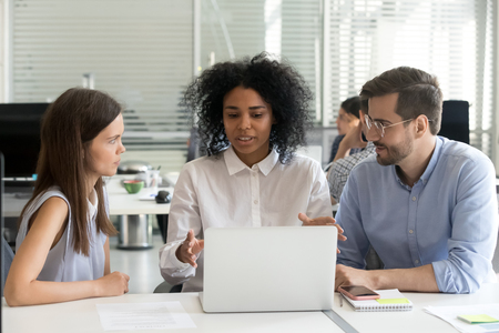 Diverse workers sitting at desk in coworking open space, african american leader at the head of team. Black skilled employee coach teaching newcomers interns explaining about new corporate application Stock Photo