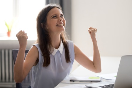 Young happy attractive woman sitting at desk opposite computer feels excitement getting monetary reward for good productive work, successful completion of project glad about signing important contract Archivio Fotografico