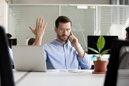 Indignant millennial employee sitting at desk in coworking space talking by mobile phone with client feels angry irritated and surprised. Office worker solves problems or business matters distantly