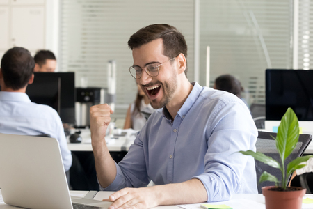 Excited worker sitting at desk in office reading notice looking at laptop screen received great unbelievable opportunity or reward gesturing I did it. Motivated employee celebrating promotion at work