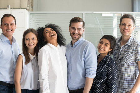 Millennial happy multi ethnic employees standing in row posing looking at camera. Six smiling successful office workers feels motivated ready for successful work and new achievements, opportunities