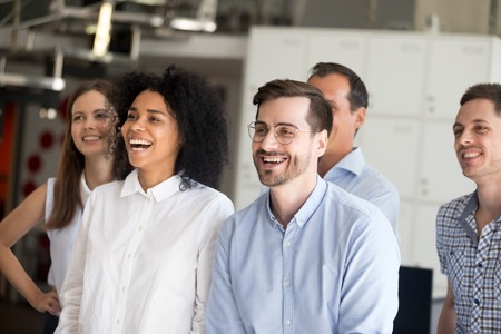 Millennial mixed race young workers or students standing together posing and laughing. Five smiling successful office employees feels happy and motivated ready for successful work and new achievements 스톡 콘텐츠