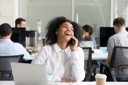 Diverse employees working in office having busy workday focus on mixed race african woman sitting at desk in coworking space talking by mobile phone feels happy has a pleasant conversation with client.
