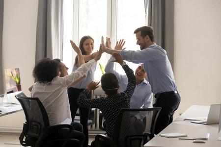 Diverse multiethnische Kollegen geben High Five und feiern Erfolg und Zielerreichung im Coworking-Büro. Glückliche tausendjährige Arbeiter schließen sich an Handflächen an und zeigen Unterstützung für Zusammengehörigkeit und Einheit Standard-Bild