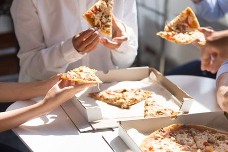 Diverse employees colleagues having break enjoy corporate lunch eating pizza in office together, close up hands of business people. Unhealthy fast food at work or delivery take away service concept