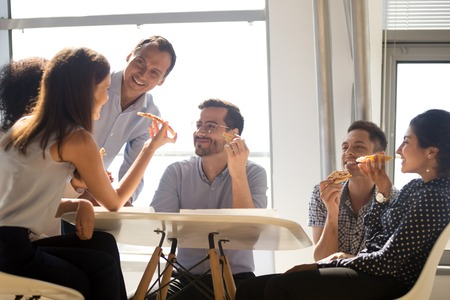 Diverse multiracial workers sitting around the office table holds slices of pizza eating junk food having pleasant conversation with coworkers. Positive millennial team enjoying break resting together