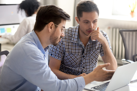 Businessman points on laptop pc explaining to newcomer about corporate application teach how to use company internal program. Coworkers working together on project sitting at desk in coworking space Stock Photo - 117645479