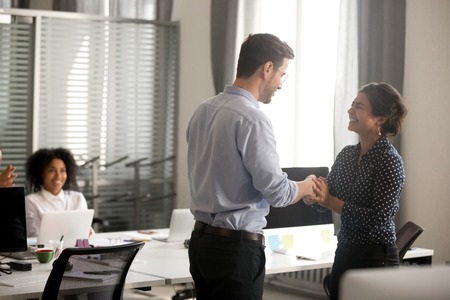 Businessman congratulate indian female successful worker shaking hands in office. Surprised hindu millennial woman feels happy proud getting promotion or reward handshaking with director company boss 写真素材