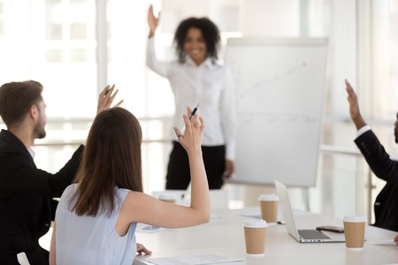 Diverse millennial team businessmen businesswomen voting raising hands making solution sitting at desk in office conference room. Concept of teamwork, unity, unanimous decision and like-minded people