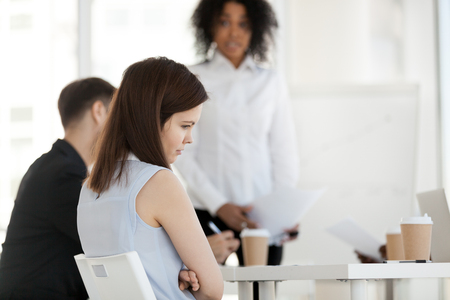 Diverse businesspeople in office during briefing focus on female worker feels guilty unhappy offended and frustrated having problem or disrespect from colleagues or made mistake, listens boss scolding Stock Photo