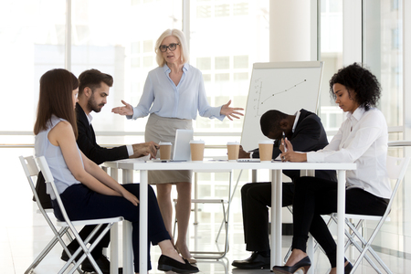 Angry dissatisfied company owner or team leader mature businesswoman scold young diverse multiracial incompetent workers. Multi-ethnic employees feel guilty made mistake which cause serious losses Stock Photo