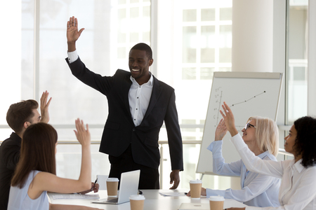 Multi-ethnic diverse millennial people smiling voting raising hands feels happy and glad making solution sitting at desk in office boardroom. Concept of teamwork, togetherness and unanimous decision Stock Photo