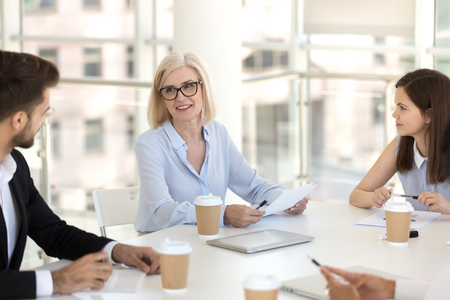 Workers headed by team leader mature female gathered together in conference room discussing business matters new project review report sales statistics sitting at desk in light modern conference room.