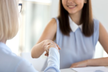 Close up of businesswomen handshaking at negotiations making great deal signing a contract. Concept of welcoming and greeting, trust and respect or human resources passing job interview successfully