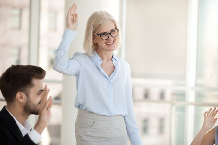 Business people raising hands voting at seminar expressing unity and unanimous decision, focus on smiling attractive positive mature experienced coach standing in front of audience during seminar