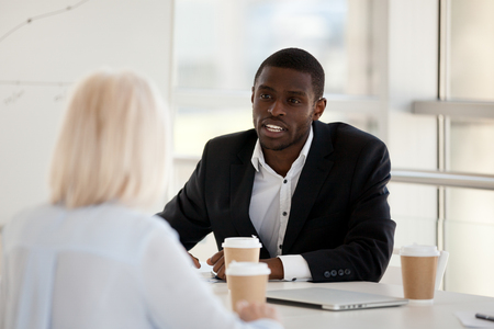 Black team leader company owner talking brainstorming with experienced colleague woman analysing market discussing project business issues. Adviser consulting client during meeting in modern office