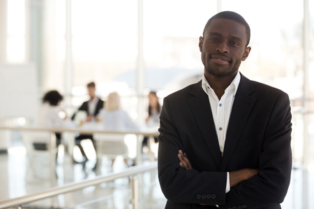 Confident black businessman in suit standing in modern office with hands crossed on chest looking at camera, workers sitting at desk on background. Leadership and successful business person concept
