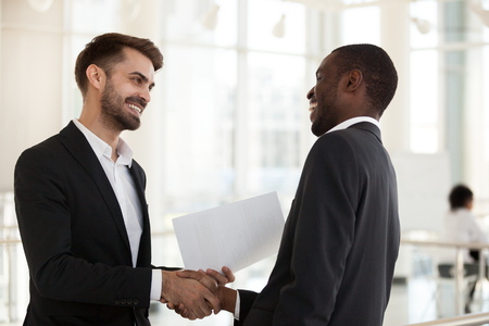 Happy diverse businessmen shaking hands after successful negotiations. Multiracial colleagues handshaking at the beginning of working day. Gesture of respect and amity, greeting and farewell concept