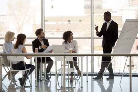 Four diverse workers and black team leader business owner gathered in boardroom during briefing in modern office. African businessmen make startup presentation or business plan for client or investor