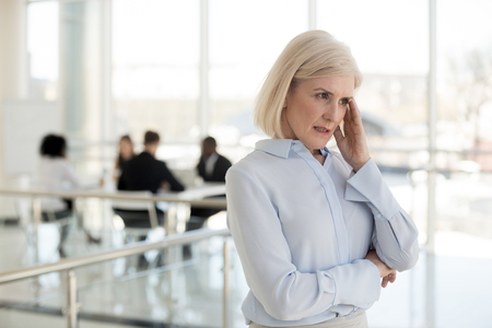 Unhappy aged business woman feels unwell suffering from headache touching massaging temple having chronic migraine during business meeting. Stressful work and overworking difficulties in job concept