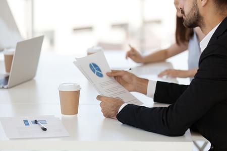 Menschen, die während des Geschäftstreffens am Schreibtisch sitzen und das finanzielle Tortendiagramm analysieren, indem sie Statistiken, Daten und Verkäufe auf Papier betrachten, konzentrieren sich auf Dokumente und Kaffeetasse. Teamwork- und Brainstorming-Konzept