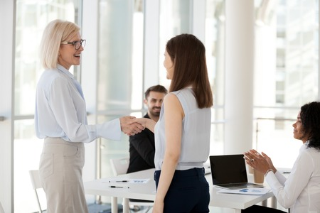Diverse happy business people gathered together in modern office conference room cheering congratulating successful colleague getting reward, promotion or greeting intern. Human resources concept Stock Photo - 117645538