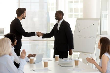 Multiracial businessmen standing in office boardroom in front of colleagues and handshaking, new employee has first workday greeting with coworkers. Boss and client shaking hands expressing respect Stockfoto