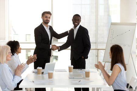 Diverse business people in boardroom, black man promoted rewarded for good job shaking hands with company director standing in front of female workers. Career development success at work concept