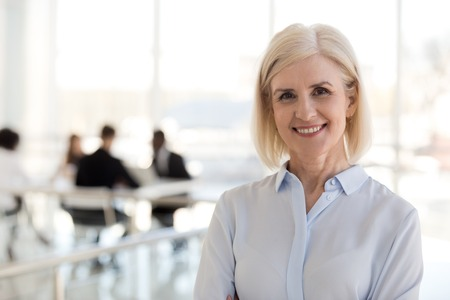 Head shot portrait of blond attractive senior woman, company president or founder standing apart of diverse workers smiling looking at camera. Team leader and leadership or women in business concept