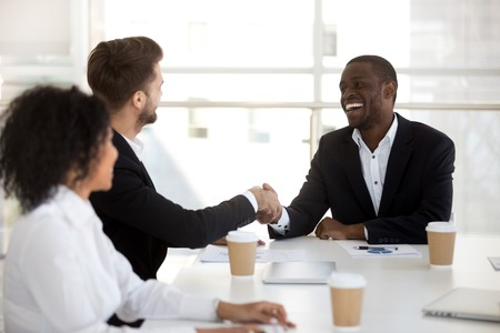 Diverse colleagues shaking hands greeting each other during briefing. Positive businessmen company owner and client handshaking expressing regard sitting together at office desk starts negotiations