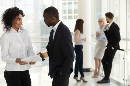 Business People take a break standing resting in modern office hallway. Workers divided by interest, focus on mixed race young female and african american male discussing having informal conversation Stock Photo