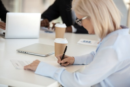 Businesspeople sitting at desk in negotiations making legal deal, mature female putting signature signing official papers contract agreement. Good result financial transaction and commitment concept Stockfoto