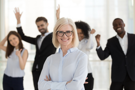 Head shot portrait successful business lady with hands crossed on chest shooting with workers diverse positive laughing employees on background. Leadership gender equality in business sphere concept
