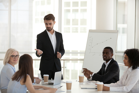 Confident coach communicating with international company staff pointing on caucasian worker female asking question. Diverse professional team members sitting in boardroom during seminar listens mentor