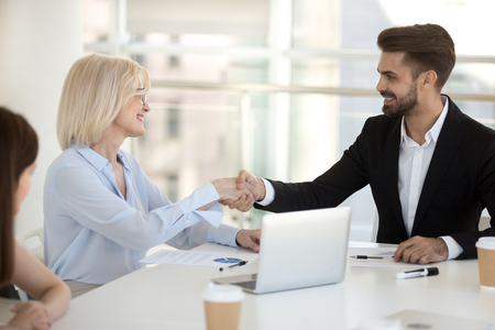 Aged businesswoman shaking hands with client greeting each other sitting at desk during meeting in office boss handshaking with new employee newcomer in company staff or congratulate promoted employee.