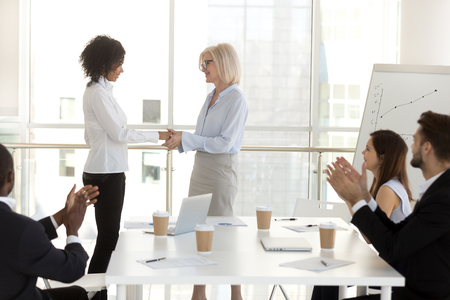 Company owner aged boss female handshaking with young biracial woman congratulating successful worker with promotion. Diverse business people colleagues applauding greeting supporting intern newcomer Stock Photo