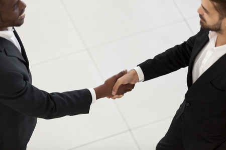 Side view diverse businessmen african black client and caucasian company owner in suits shaking hands before negotiations, close up focus on handshake. Gesture of respect partnership diplomacy concept